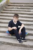 En tonåring med en skateboard Sitter på en skateboard mot bakgrunden av en stentrappuppgång Arkivbilder