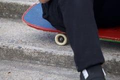 En tonåring med en skateboard Sitter på en skateboard mot bakgrunden av en stentrappuppgång Royaltyfri Fotografi