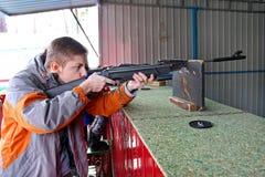 En tonåring siktar ut ur ett gevär på det fria för en skjutbana royaltyfri bild