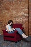 En tonåringflicka skriver i ett dagbokanteckningsboksammanträde i en gammal stol på en dyster övergiven station med en tegelstenv Arkivfoto