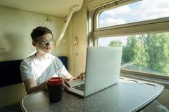 En tonåringpojke på ett drev sitter på en tabell med en öppen dator royaltyfri fotografi
