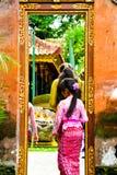 En tonårs- flicka för Balinese som bär traditionella lokala kläder som skriver in en sakral tempel arkivbilder