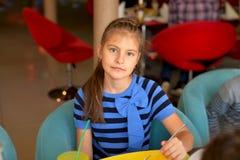 En tonårs- flicka i blåsvart klänning med en pilbåge har lunch i ett kafé royaltyfri foto