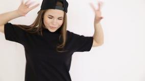 En tonårs- flicka i svart höft-flygtur kläder och ett lock dansar på den vita väggnärbilden, den handheld forsen, litet djup av lager videofilmer