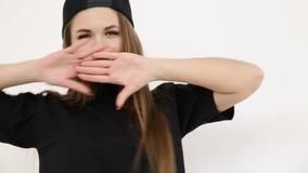 En tonårs- flicka i svart höft-flygtur kläder och ett lock dansar på den vita väggnärbilden, den handheld forsen, litet djup av stock video