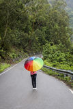 En tonårs- flicka med det färgrika paraplyet arkivbilder
