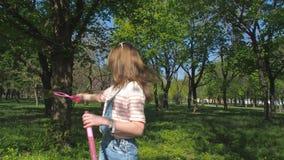 En tonårs- flicka med såpbubblor i parkera Flicka på en solig dag i den nya luften Ett barn spelar med bubblor i natur arkivfilmer