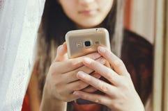 En tonårs- flicka rymmer en mobiltelefon närbild mjuk fokus royaltyfri fotografi