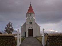 En torvvägg framme av en liten kyrka i Island royaltyfri fotografi