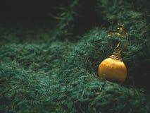 En toy på entree med porslin Jultomte och gran - tree Gul julboll på en mjuk grön bakgrund arkivfoton