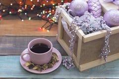 En träask med prydnader och en kopp för rosa te med ett tefat Royaltyfria Foton