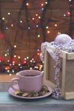 En träask med prydnader och en kopp för rosa te med ett tefat Royaltyfri Bild