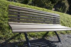 En träbänk på en bana i parkera Arkivfoto