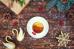 En träbakgrund med julpynt En kopp av varmt te med citronen festligt kort för xmas Nytt år feriebegrepp royaltyfria bilder