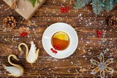 En träbakgrund med julpynt En kopp av varmt te med citronen festligt kort för xmas Nytt år feriebegrepp arkivbilder