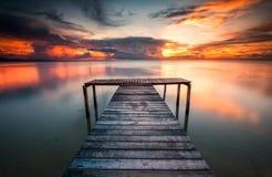 En träbrygga med ljus solnedgångbakgrund Arkivfoton
