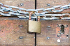 En trädörr låste med en kedja och en rostig hänglås Arkivfoto