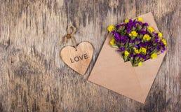 En trähjärta och ett kuvert med ljusa lösa blommor letter romantiker Romantiskt begrepp Arkivfoton
