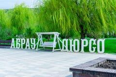 En träinskrift av Abrau-Durso av vit färg och en rymlig gunga mellan orden mot bakgrunden av gräsplan fotografering för bildbyråer