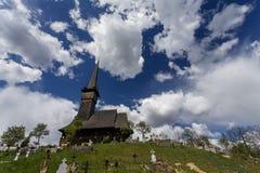 En träkyrka i Maramures, Rumänien som profileras på blå himmel med Arkivfoton