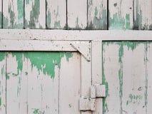 En träsköld av vit färg, med slats för vit metall och lappar av skalningsgräsplanmålarfärg, en abstrakt bakgrund med en tappning  Royaltyfri Foto