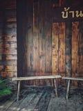 En trästol som placeras på den thailändska traditionella trähusterrassen med ett hus, undertecknar in thailändskt språk Arkivbild