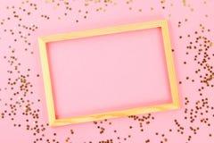 En trätom ram på en pastellfärgad bakgrund som omges av skinande dekorativa stjärnor och bollar Royaltyfri Foto