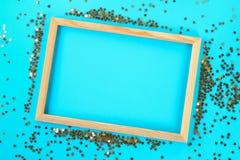 En trätom ram på en pastellfärgad bakgrund som omges av skinande dekorativa stjärnor och bollar Arkivfoto