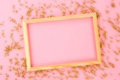 En trätom ram på en pastellfärgad bakgrund som omges av skinande dekorativa stjärnor och bollar Royaltyfri Fotografi