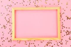En trätom ram på en pastellfärgad bakgrund som omges av skinande dekorativa stjärnor och bollar Royaltyfria Foton