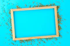 En trätom ram på en pastellfärgad bakgrund som omges av skinande dekorativa stjärnor och bollar Fotografering för Bildbyråer