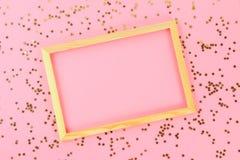 En trätom ram på en pastellfärgad bakgrund som omges av skinande dekorativa stjärnor och bollar Arkivfoton