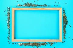 En trätom ram på en pastellfärgad bakgrund som omges av skinande dekorativa stjärnor och bollar Royaltyfria Bilder