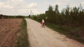 En trött flicka med en korg rider en cykel på vägen stock video