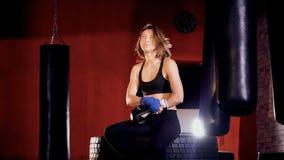 En trött kvinnlig boxare tar av hennes handskar lager videofilmer