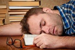 En trött och torterad ovårdad student med exponeringsglas sover på en tabell arkivbild