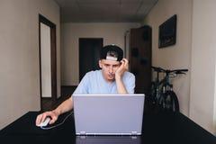 En trött student stirrar på anteckningsbokbildskärmen i rummet av hans hem Teen lokal Arkivfoto
