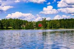 En traditionell finlandssvensk trästuga med en bastu och en ladugård på sjökusten Sommar lantliga Finland Arkivfoton