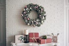 En traditionell ljus julkrans som hänger över spisen, på en vit tegelstenvägg och emballerade gåvor staplas royaltyfria bilder