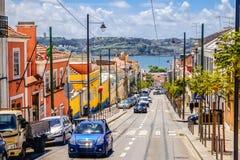 En trafik av lutningsgatan i Lissabon med färgrika byggnader längs vägrenen och en havssikt arkivbild