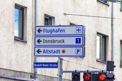 En trafikljus med pilar och en utgång undertecknar för huvudvägar 1 i riktningen av Innsbruck, flygplatsen och den gamla staden Royaltyfria Bilder