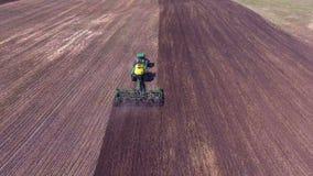 En traktor kör långsamt på ett stort fält stock video