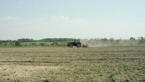 En traktor med en odlare fungerar jorden för att plantera arkivfilmer