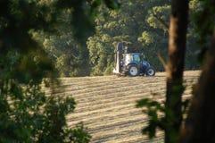 En traktor på en lantgård till och med träden Royaltyfria Foton