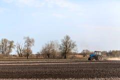 En traktor plogar ett fält för att så skördar royaltyfria foton