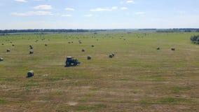 En traktor rider till och med ett fält med hö, bästa sikt stock video