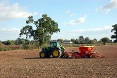 En traktor sår kärnar ur i ett fält Arkivfoto