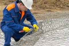 En travaillant dans un uniforme bleu, tricotez la maille pour des cellules sous les pierres pour améliorer le rivage, plan rappro photos libres de droits