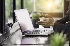 En travaillant sur l'ordinateur portable, fermez-vous des mains de l'homme d'affaires image libre de droits