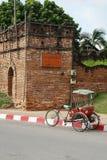 En trehjuling och en antikvitetvägg Arkivbild